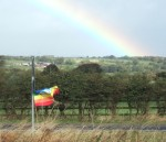the rainbow meant the rain was dying out but the flapping of the rainbow peace flag is indicative of the strong winds