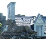 a stone dog & roofs close by the castle ruins