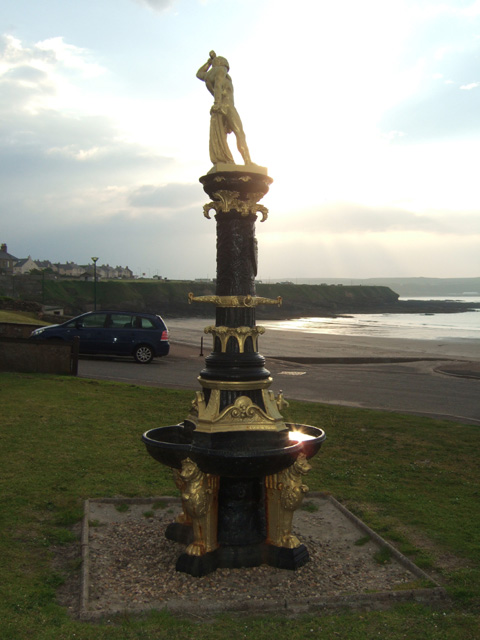 an elaborate fountain close by the sea