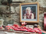 a splendid collection of red cars overseen by a photo of their daughter Kate