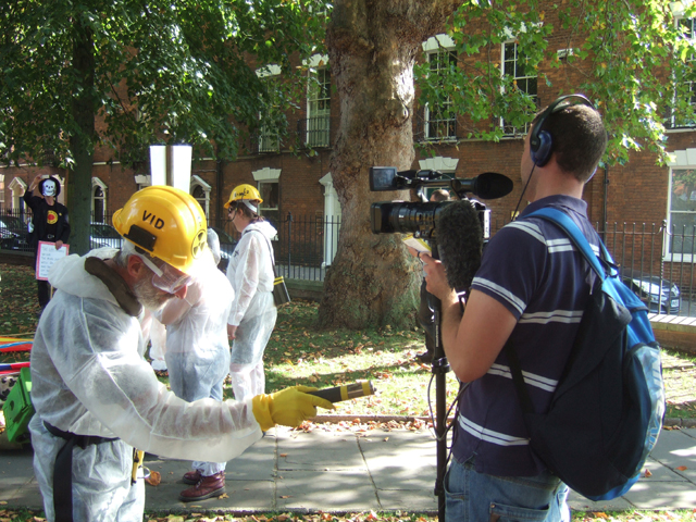 and a man in a white contamination suit with a geiger counter, here checking out a cameraman