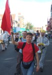 here a demonstrator with a socialist red flag followed by a group in decomination suits with one using a megaphone to say, 'Do not be alarmed, stay in your houses...'etc.
