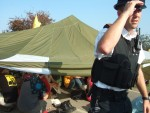 a police officer steadying his helmet after he'd had to duck under the tent