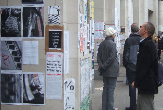 reading the poster wall - the columns of the shopping arcade have been used for voicing a variety of information and ideas