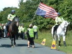 Lindis with the upside-down American flag, a symbol of protest around the world, talking to a police horse rider