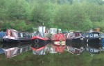 canal boats perfectly mirrored in the still waters